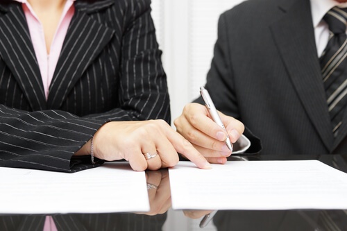 Photo of lawyer with couple, working on a Separation Agreement, just one of many legal agreements that are regularly handled by the lawyers and attorneys in the Edmonton law offices of The Family Law, serving clients in Alberta and beyond
