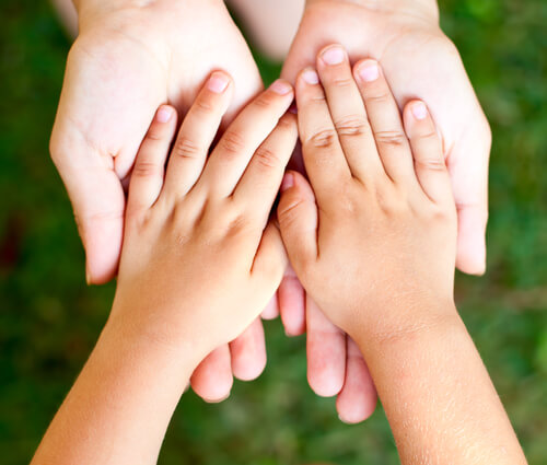Photo of parent supporting the hands of a child, which underlines the importance of child support, an area of Family Law handled by the lawyers who can answer your questions about child support guidelines.